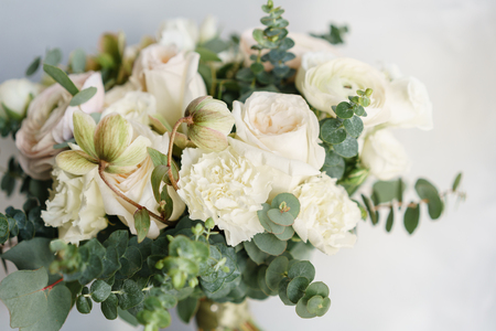 Wedding bouquet of white roses and buttercup on a wooden table. Lots of greenery, modern asymmetrical disheveled bridal bunch