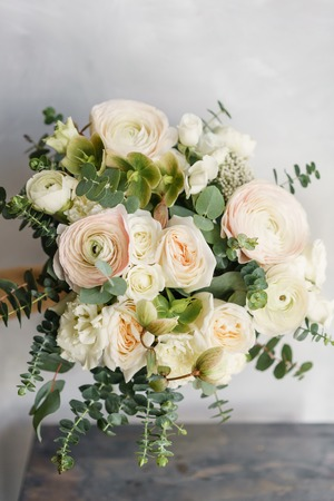 Wedding bouquet of white roses and buttercup on a wooden table. Lots of greenery, modern asymmetrical disheveled bridal bunch Foto de archivo - 100058534