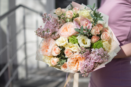 bouquet of beautiful flowers in womens hands. Floristry concept. Spring colors. the work of the florist at a flower shop. Horizontal photo