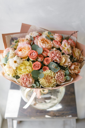pastel orange and pink bouquet of beautiful flowers on wooden table. Floristry concept. Spring colors. the work of the florist at a flower shop. Vertical photo