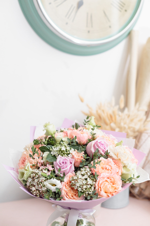 pastel orange and lilac bouquet of beautiful flowers on wooden table. Floristry concept. Spring colors. the work of the florist at a flower shop. Vertical photo Stock Photo