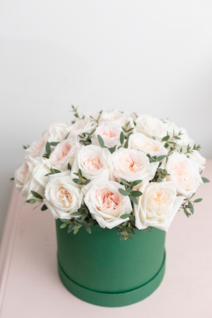 White and pink roses. Bouquet of beautiful flowers on wooden table. Floristry concept. Spring colors. the work of the florist at a flower shop. Vertical photo Stock Photo