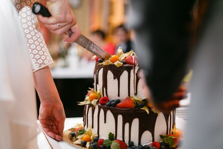 Wedding cake with berries on wooden table. Bride and groom cut sweet cake on banquet in restaurant.