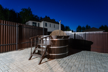 rural wooden water hot tub with stairs garden yard. . night and starry sky