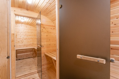 interior of sauna. rural mobile wooden bath in the form of a barrel in a pine forest