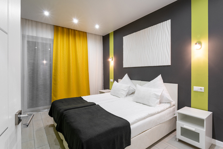 Hotel standart room. modern bedroom with white pillows. simple and stylish interior. interior lighting Фото со стока