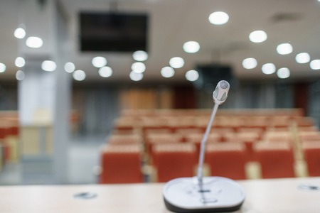 microphone in the foreground. Seminar presentation. Conference room full of empty seats. Red color. Hall for workshops and seminars