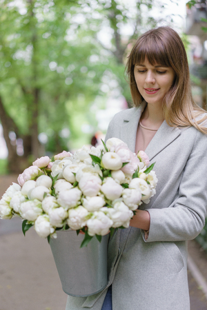 Beautiful bouquet of white peonies in woomans hands . Floral composition, daylight. Wallpaper. Vertical photo