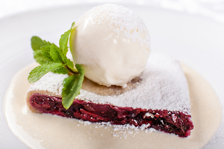 berry strudel cake served with ice cream, mint leaf and vanilla sauce. Classical austrian dessert on white plate. Sweet dessert in the restaurant. Morning light.