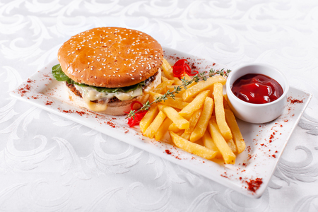 Fast food restaurant menu. Home made hamburger with the beef patties, onion, tomato, lettuce and cheese. Fresh burger close-up. Garnished with golden French fries potatoes Stock Photo