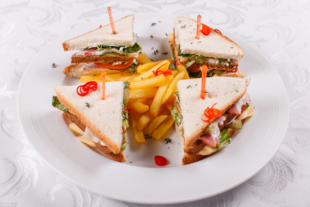 Fast food restaurant menu. Club sandwich with cheese, pIckled cucmber, tomato and smoked meat. Garnished with golden French fries potatoes