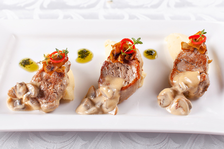 Pork Medallions with Mashed Potato and Mushrooms. Pork tenderloin on a white plate, good serving. restaurant menu