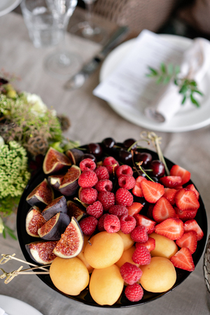Fresh Fruit platter on banquet table at business or wedding event venue. Self service or all you can eat - raspberry, strawberry, cherry, Fig, apricote. Table with cold snacks and tableware Reklamní fotografie