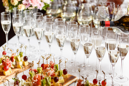 Bartender pouring champagne or wine into wine glasses on the table in restaurant. solemn wedding ceremony or happy new year banquet Stock Photo