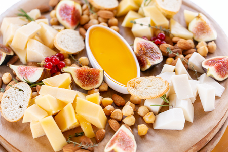 Cheese plate. Delicious cheese mix with baguette croutons, red currant, sweet figs, almond, honey on wooden table. Tasting dish on a wooden plate. Food for wine. Goat cheese, Parmesan, Gouda