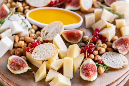 Light Italian snacks. A buffet table at a dinner party. Cheese plate. Delicious cheese mix on wooden table. Tasting dish on a wooden plate. Food for wine. Reklamní fotografie