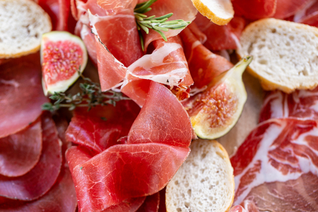 Light Italian snacks. A buffet table at a dinner party. Food tray with delicious salami, pieces of sliced ham, sausage. Cutting sausage and cured meat on a celebratory table.