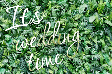 Decorate wall backdrop of artificial leaf and shiny letters. It is wedding time
