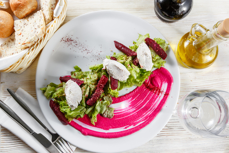 Healthy italian salad with beetroot, lettuce leaves and cheese feta and dressing with oil and mustard seeds.