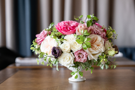 Arrangement of fresh flowers in pastel colors with a bright accent. Wedding background. table in a restaurant. different varieties of garden and shrub roses in a light vase on wooden table