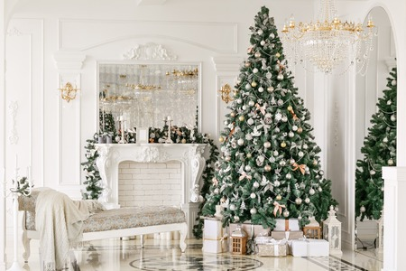 gifts at the Christmas tree. Christmas morning. classic luxurious apartments with a white fireplace, sofa, large windows and chandelier.