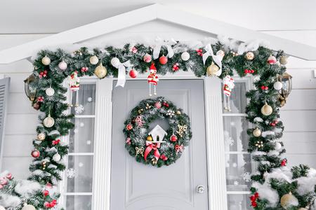 Weihnachtsmorgen. Hauseingang für Feiertage dekoriert. Weihnachtsdekoration. Girlande aus Tannenzweigen und Lichtern am Geländer