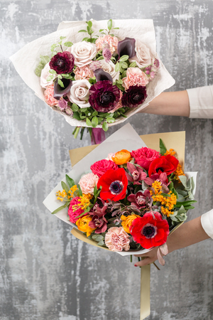 two beautiful bouquet of mixed flowers in woman hand. the work of the florist at a flower shop