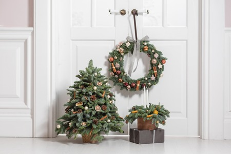 Decoration of the house before the new year holidays. Set of decorative elements with fir branches wreath, Christmas tree and arrangement in a wooden box Stockfoto