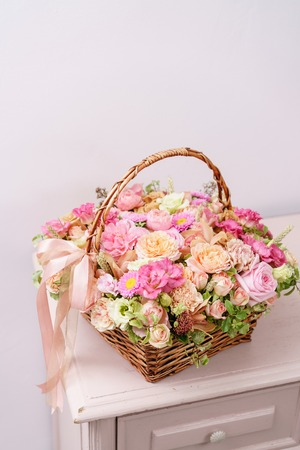 flowers arrangement with various of colors in wicker basket on pink table. beautiful spring bouquet. bright room, white wall. copy space