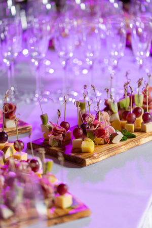 the buffet at the reception. Assortment of canapes on wooden board. Banquet service. catering food, snacks with cheese, jamon, prosciutto and fruit Stock Photo