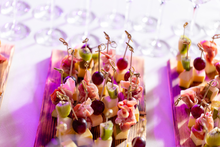 Light snacks in a plate on a buffet table. Assorted mini canapes, delicacies and snacks, restaurant food at event. A gala reception. Decorated delicious table for a party goodies. Stockfoto