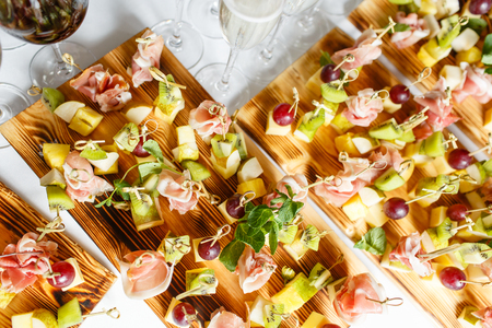 Light snacks in a plate on a buffet table. Assorted mini canapes, delicacies and snacks, restaurant food at event. A gala reception. Decorated delicious table for a party goodies. Фото со стока
