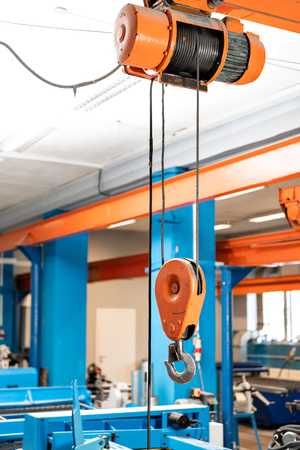 Crane hook. The system of pulleys and ropes, a hanging mechanism in the production area. Movement remote control pendant switch for overhead crane in the factory Stock fotó