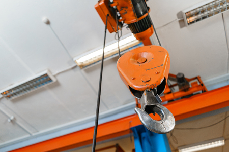 Crane hook. The system of pulleys and ropes, a hanging mechanism in the production area. Movement remote control pendant switch for overhead crane in the factory