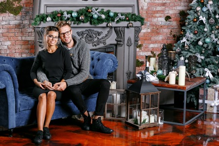Young beautiful couple In loft room with brick wall. Happy new year. decorated Christmas tree Imagens