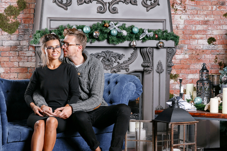Young beautiful couple In loft room with brick wall. Happy new year. decorated Christmas tree 版權商用圖片