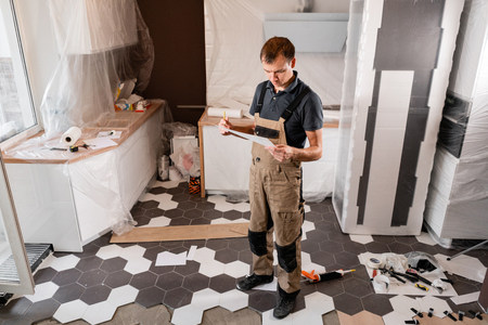 Focused diligent worker inspecting room and planning repairs work. repair of the dining room in the house, kitchen furniture, floor covering change