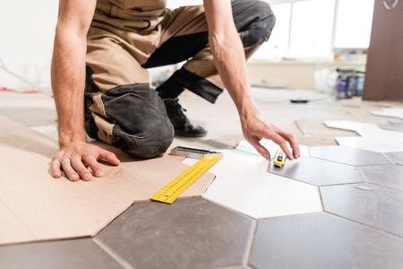 Trabajador masculino toma medidas e instala nuevos pisos laminados de madera. La combinación de paneles de madera de laminado y baldosas cerámicas en forma de panal. Renovación de cocina.