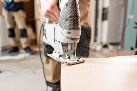 Male worker cuts the laminate Board with an electrofret saw. installing new wooden laminate flooring. concept of repair in house.