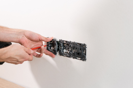 Electrician worker installs light switch and socket on wall in White room. Screwdriver, close-up electrician hands.