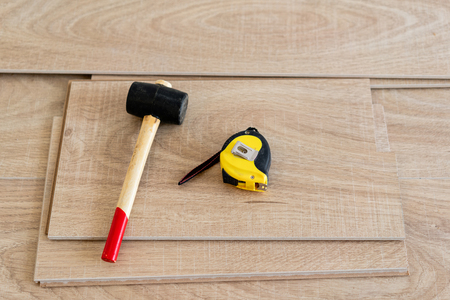 Installing laminate parquet in interior. On the floor lie different carpenter tools. Hammer and measuring tape. concept of repair in house.