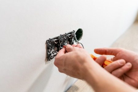 electrician connects the sockets to the electrical wires on wall in White room. Screwdriver, close-up electrician hands. 版權商用圖片