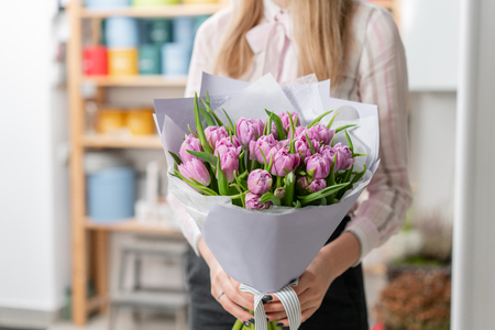 Sunny spring morning. Young happy woman holding a beautiful bunch of lilac tulips in her hands. Present for a smiles girl. Banco de Imagens