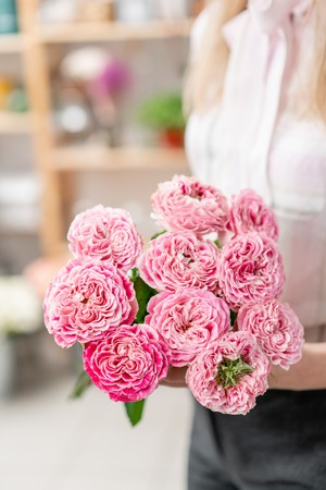 Garden roses bright pink and pastel colors. Bright bouquet in the hands of a cute girl.