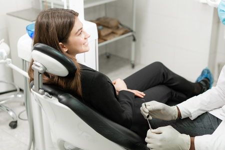young beautiful girl in the dentist chair at dental clinic. Medicine, health, stomatology concept. dentist treating a patient. Woman smiling