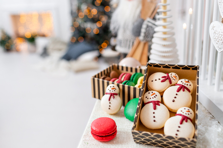 Variety of sweet macaroons in carton box. Cookie in the form of a snowman. Merry Christmas card. New year mood. lights of garland bulbs