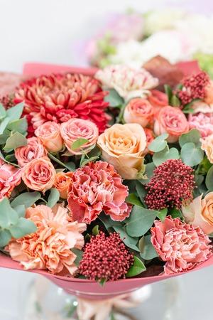 Europese bloemenwinkel. Boeket Gemengde mooie bloemen op houten grijze tafel. Leuke tuinbloemen in het arrangement, het werk van een professionele bloemist. Stockfoto