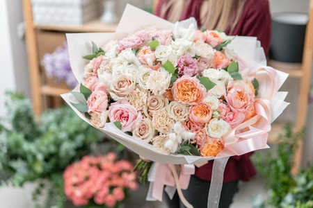 European floral shop. Bouquet of beautiful Mixed flowers in woman hand. Excellent garden flowers in the arrangement , the work of a professional florist. 免版税图像