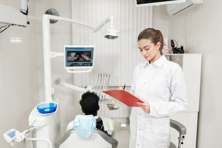 Charming beautiful girl doctor dentist. Young African American male patient at chair at dental clinic. Medicine, health, stomatology concept. dentist conducts inspection and concludes. Woman smiling