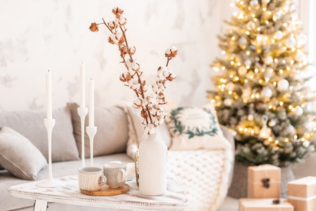 vase with cotton branches. Light living room with Christmas tree. Comfortable sofa, high large Windows